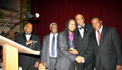 Taj Weekes receiving St. Lucia House Foundation's Distinguished Humanitarian award from the Minister of Foreign Affairs & International Trade & Civil Aviation