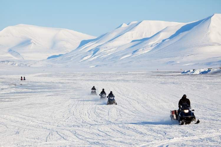 A group of snowmobiles on the ice outside Longyearbyen, Svalbard, Norway.