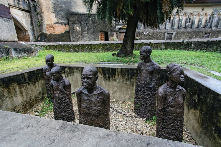 Slavery monument with sculptures and chains near the former slave trade place in Stone town, Zanzibar