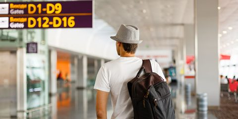 The man in the hat in the airport, business travel, passenger looking at timetable screen board