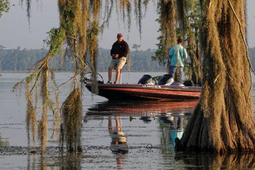 Fishermen in the morning light of the Bayou. Lake Martin, in St. Martin Parish, is a wildlife preserve and one of Louisiana swamplands.