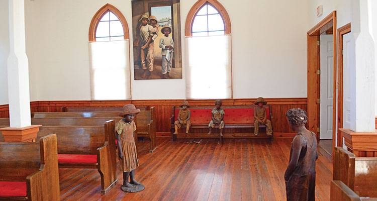 Terra-cotta statues of child slaves are inside of a church at the Whitney Plantation